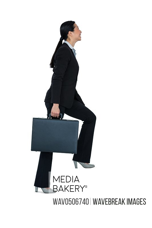 Businesswoman with briefcase walking on stairs against white background