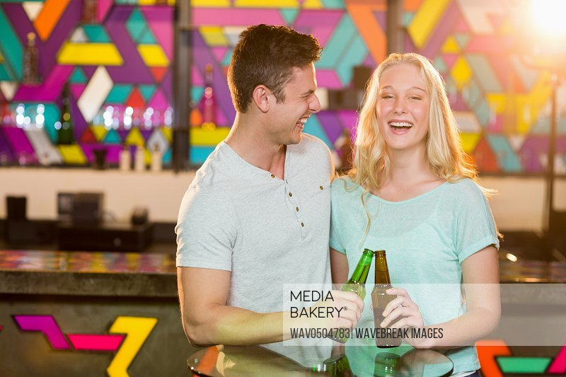 Happy couple toasting a beer bottles in bar