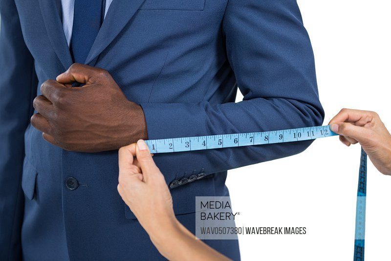 Mid section of woman measuring businessman sleeve on white background