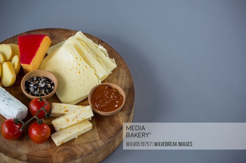 Variety of cheese with cherry tomato sauce and spices on wooden board