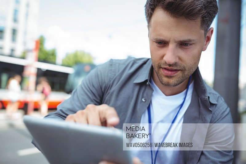 Close-up of handsome business executive using digital tablet