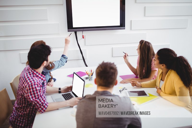 Young executives looking at television in creative office