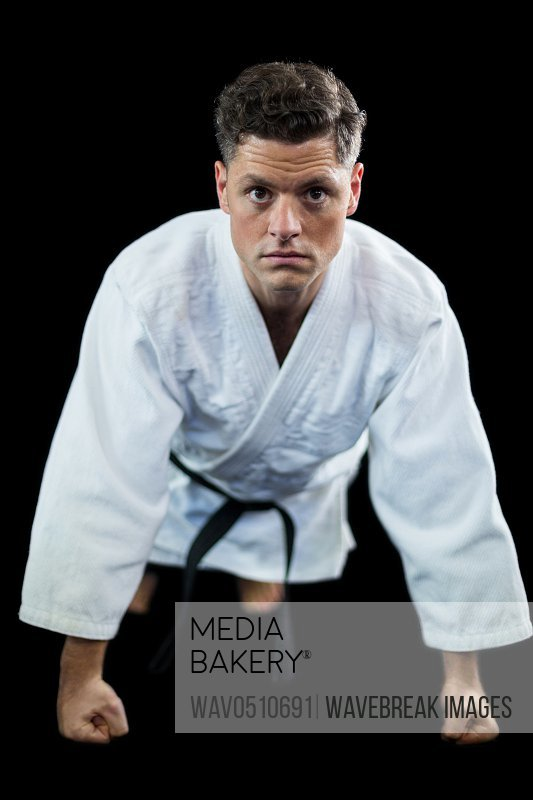 Karate player doing push-up against black background