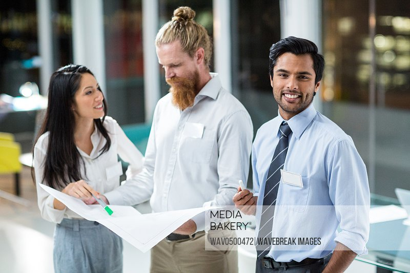 Businessman smiling at camera while colleagues discussing over blueprint in the office