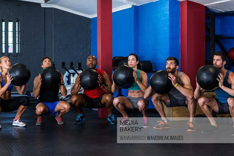 Friends holding exercise ball while crouching in gym