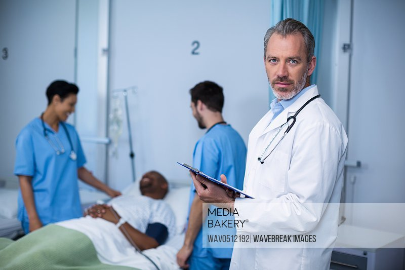 Portrait of doctor writing on clipboard during visit in ward