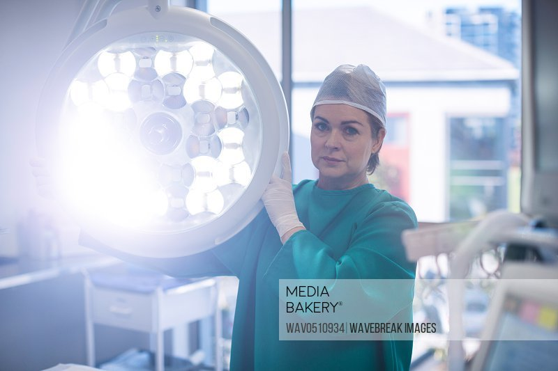 Portrait of surgeon adjusting surgical light in operation room at hospital