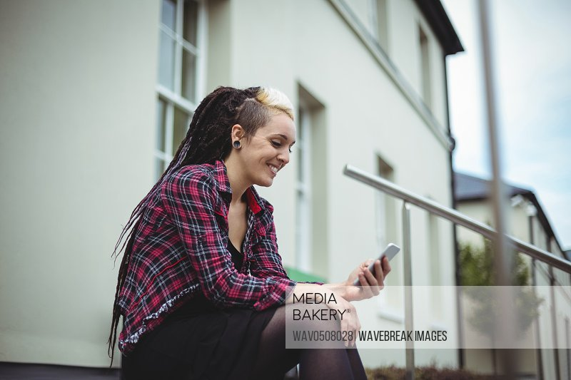 Woman using mobile phone in office campus