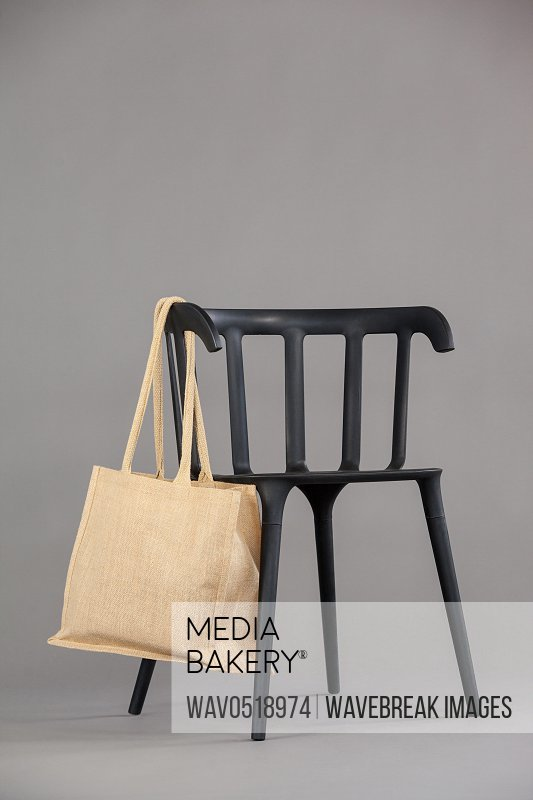 Beige colored shopping bag hanging on black chair