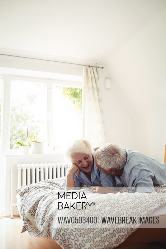 Senior couple interacting while relaxing on bed in bedroom