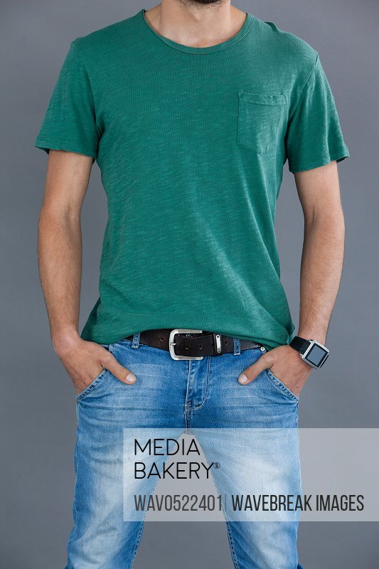 Man in green t-shirt posing with hands in pockets
