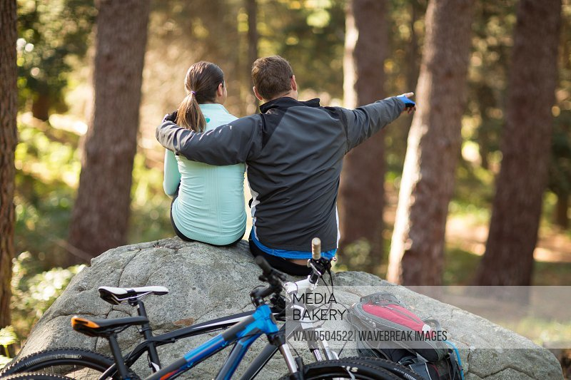 Biker couple sitting on rock pointing at distance in forest at countryside