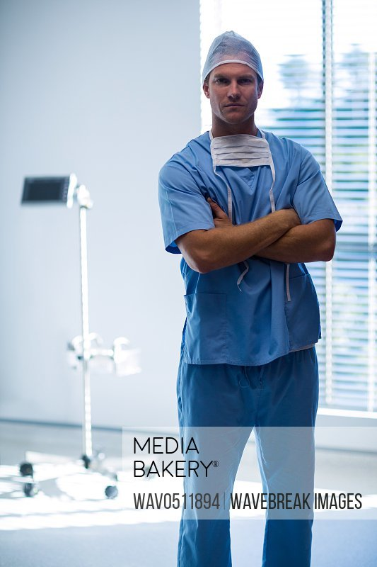 Portrait of male nurse standing with arms crossed in corridor of hospital