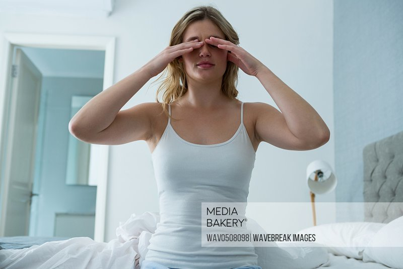 Young woman waking up from sleep in bedroom at home