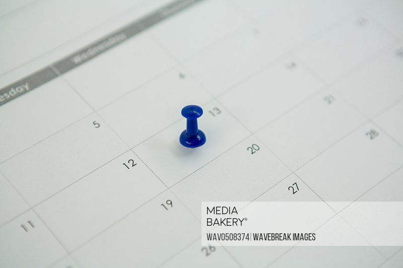 Close-up of blue push pin marked on calendar