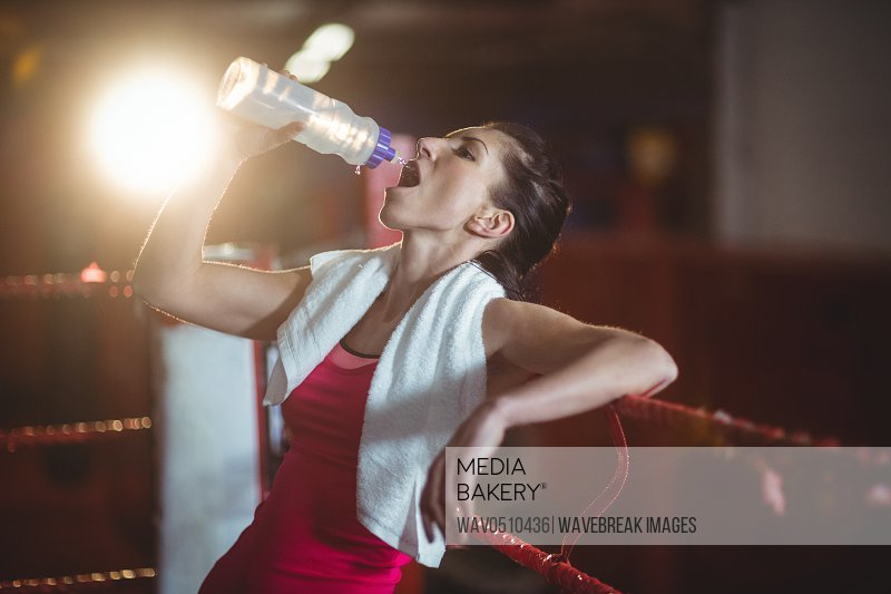 Female boxer drinking water from bottle in boxing ring