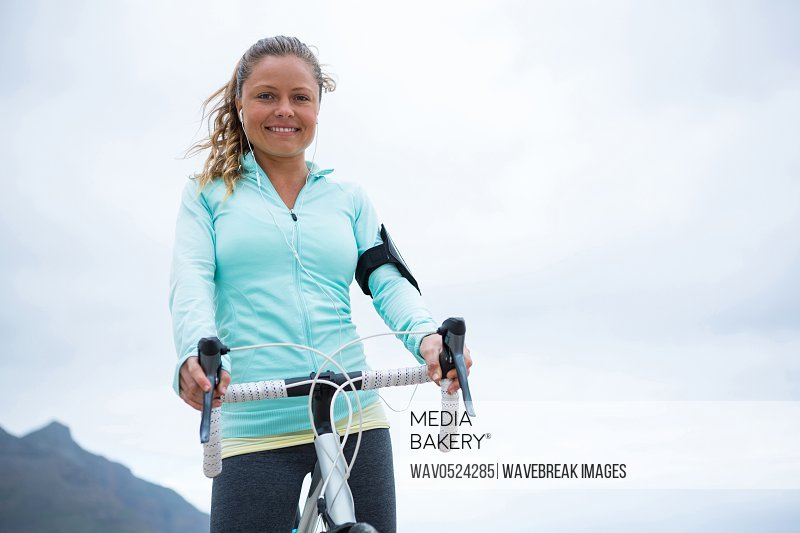 Portrait of happy woman standing with bicycle on beach