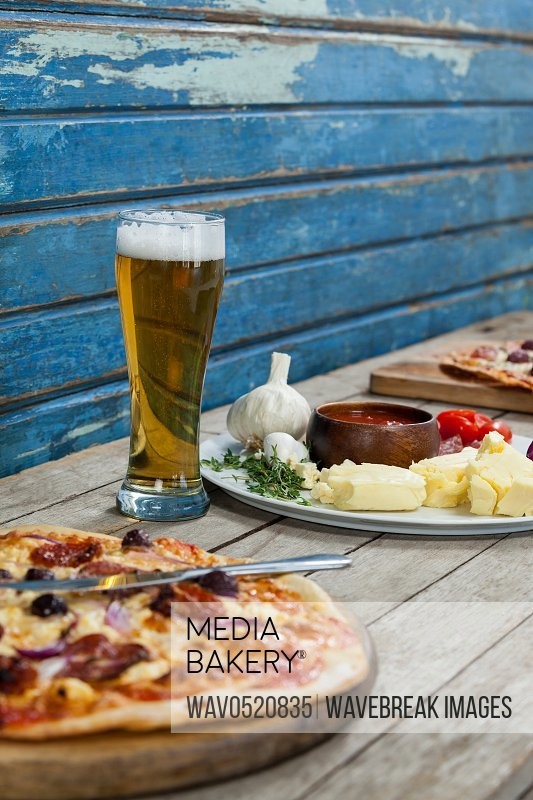 Italian pizza served with glass of beer on wooden plank