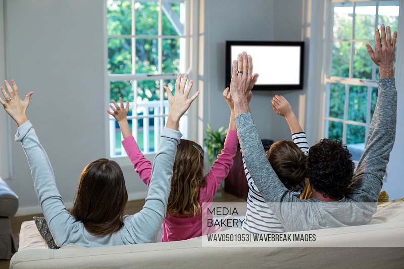 Family raising hands while watching television at home