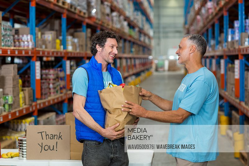 Portrait of happy volunteers holding a grocery bag in a warehouse