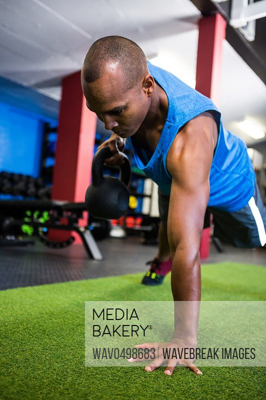 Young man holding kettlebell while exercising in gym