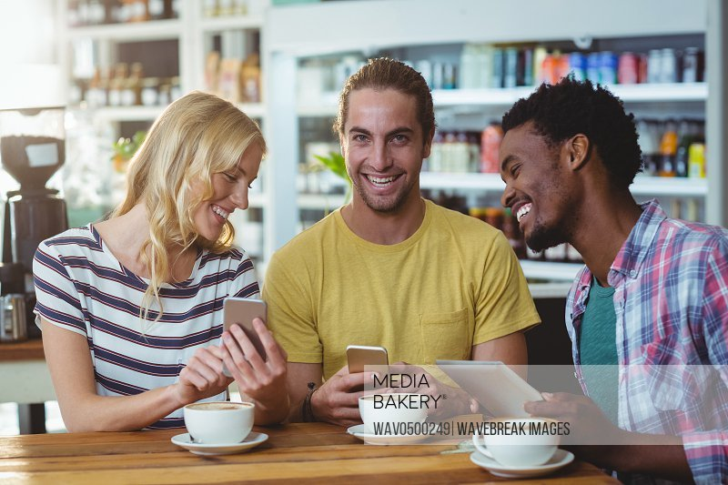 Three friends using mobile phones while having cup of coffee in cafe