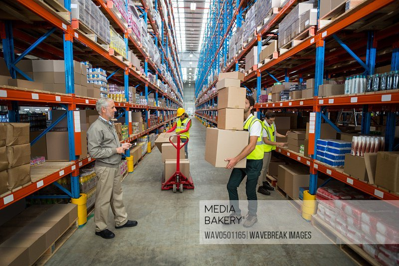 Manager looking at the worker carrying cardboard boxes in warehouse