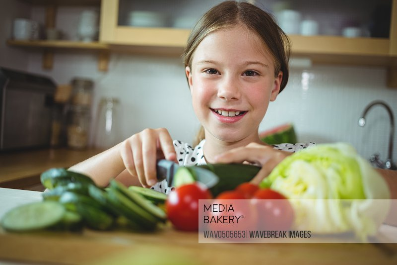 Portrait of girl cutting zucchini in kitchen at home