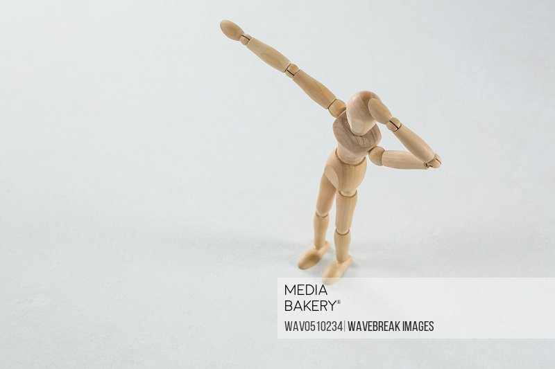 Wooden figurine shocked and pointing against white background
