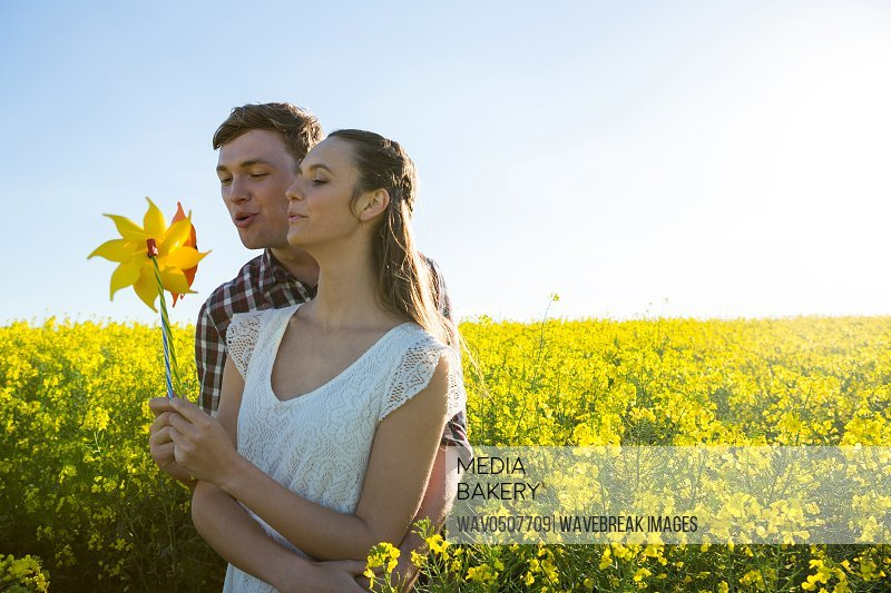 Couple holding blowing pinwheel in mustard field on a sunny day