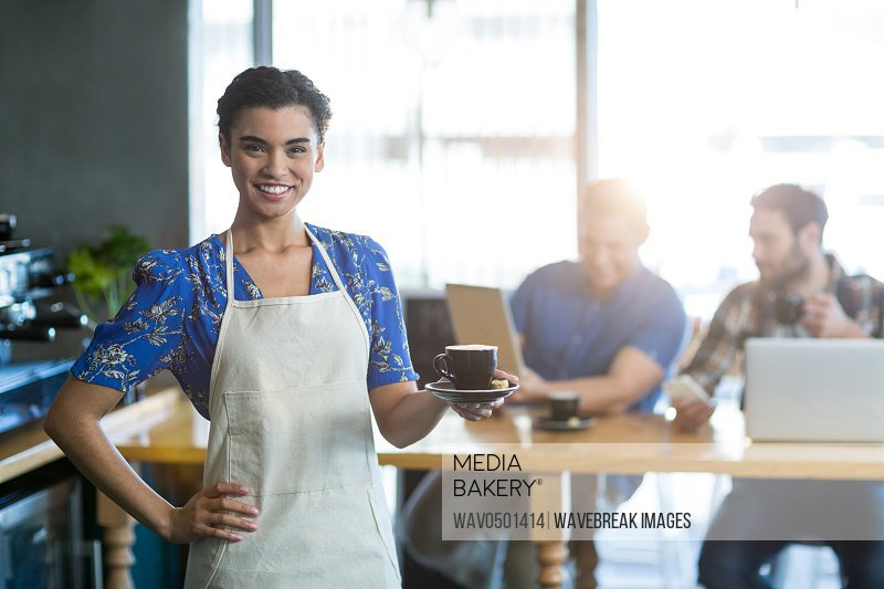 Portrait of waitress holding cup of coffee in cafA?