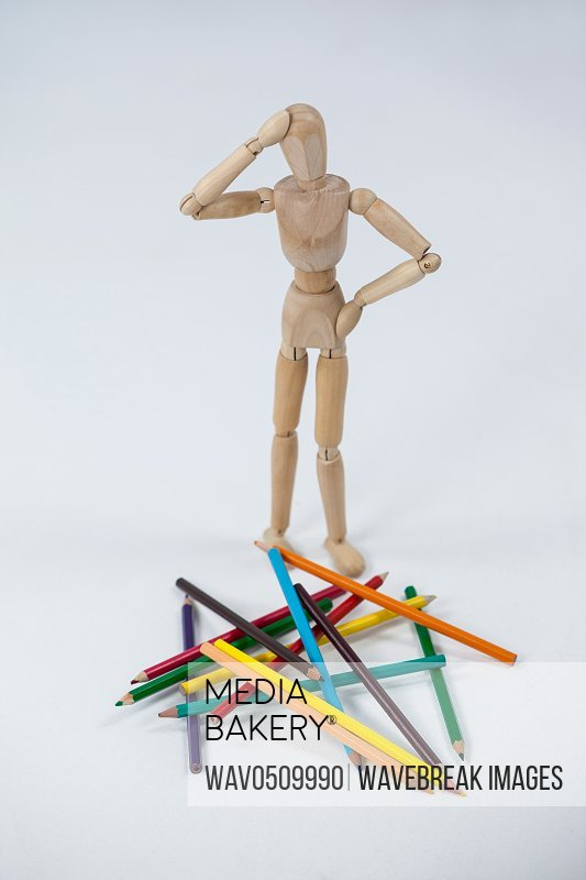 Confused wooden figurine standing near a heap of color pencils against white background