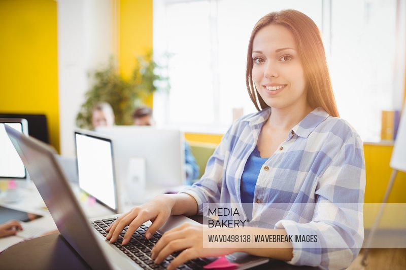 Portrait of happy female graphic designer working with laptop in creative office