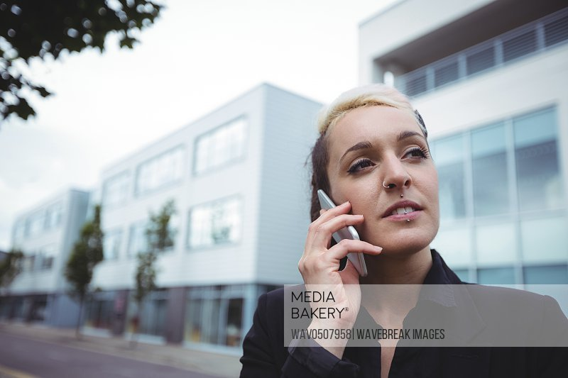 Businesswoman talking on mobile phone in office campus