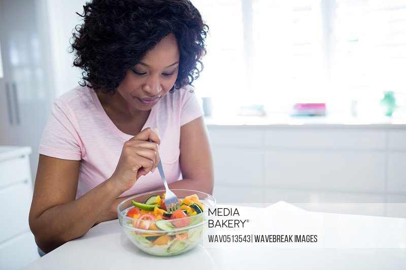 Woman on diet eating salad in kitchen