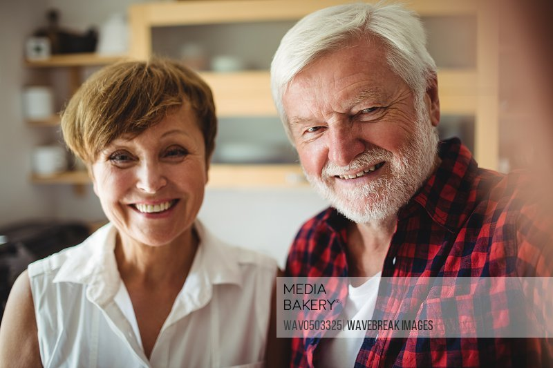 Portrait of senior couple smiling in kitchen at home