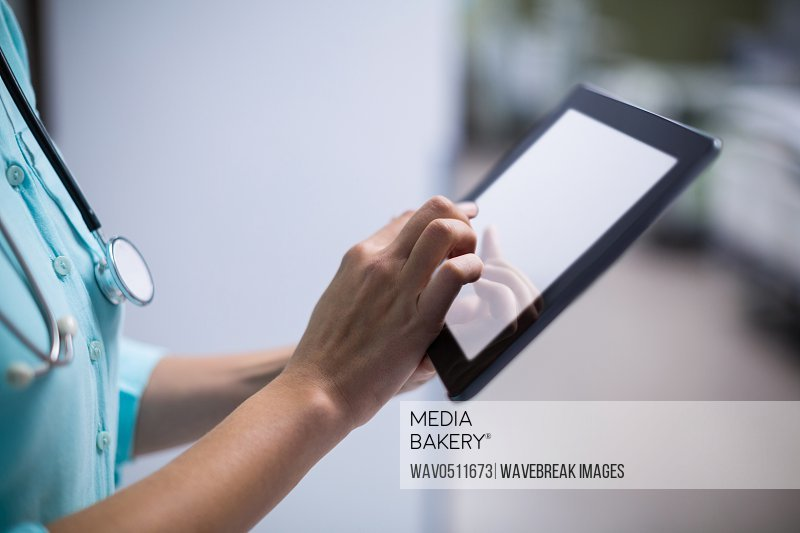 Mid section of female doctor using digital tablet in corridor of hospital