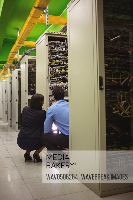 Technicians analyzing server in server room