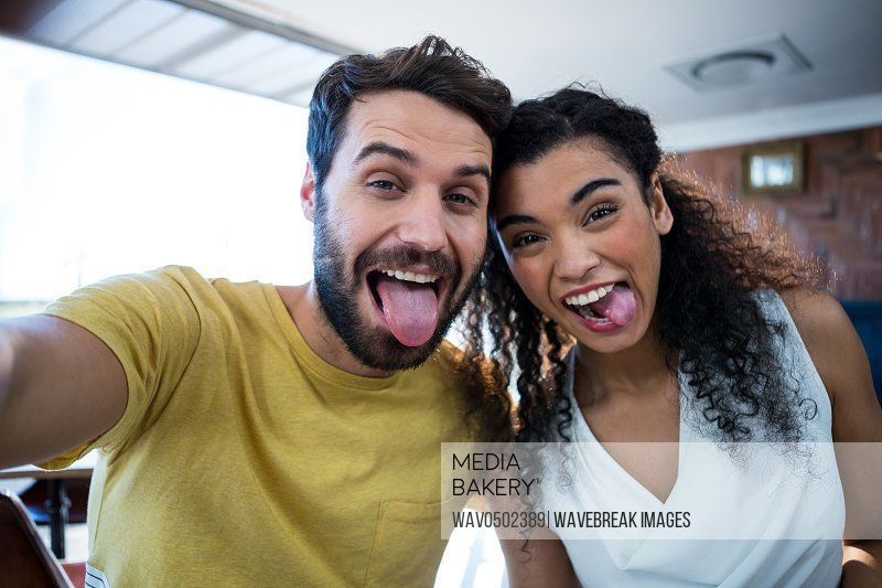 Couple making facial expression and having fun in coffee shop
