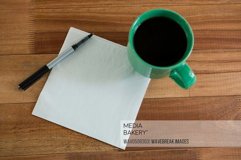 Close-up of coffee mug with blank paper and pen on table in office