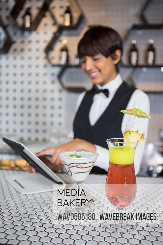 Waitress using digital tablet with glass of cocktail in bar counter at bar