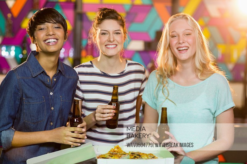 Portrait of smiling female friends having bottle of beer and pizza in party at bar