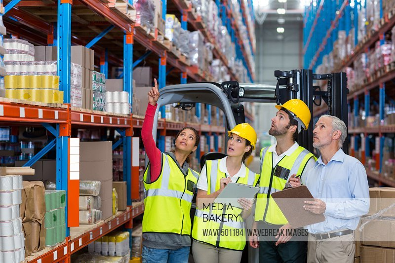 Warehouse manager and co-workers discussing over clipboard in warehouse