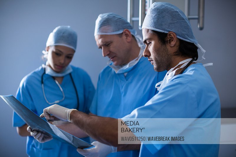 Surgeons discussing over x-ray at hospital