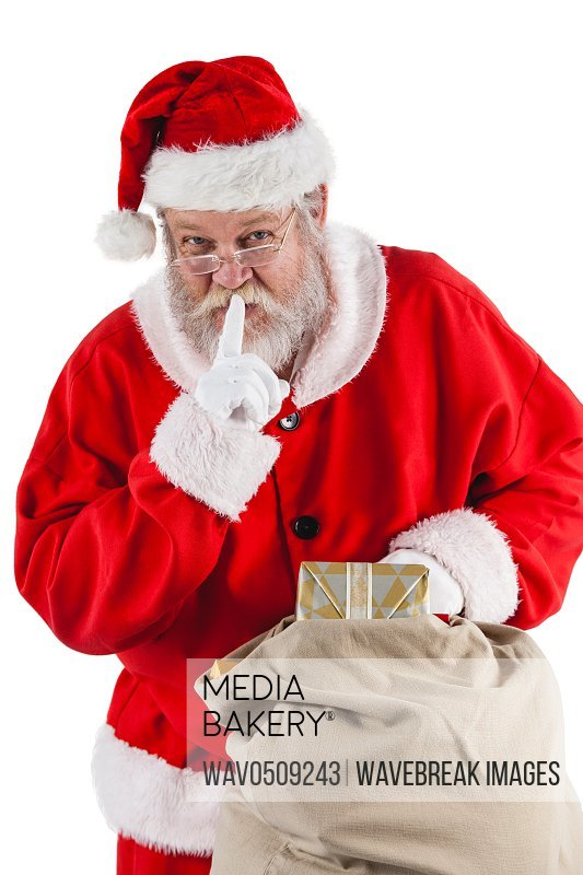 Santa claus with finger on lips and holding a gifts