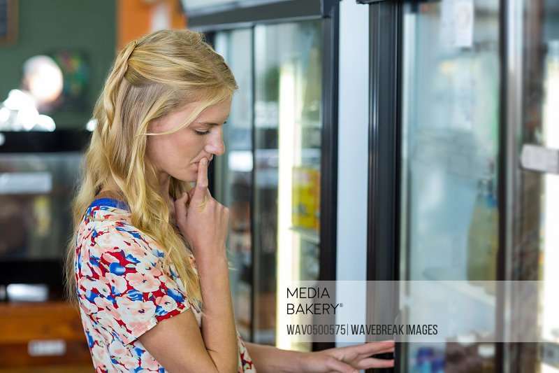 Woman looking at refrigerator in supermarke