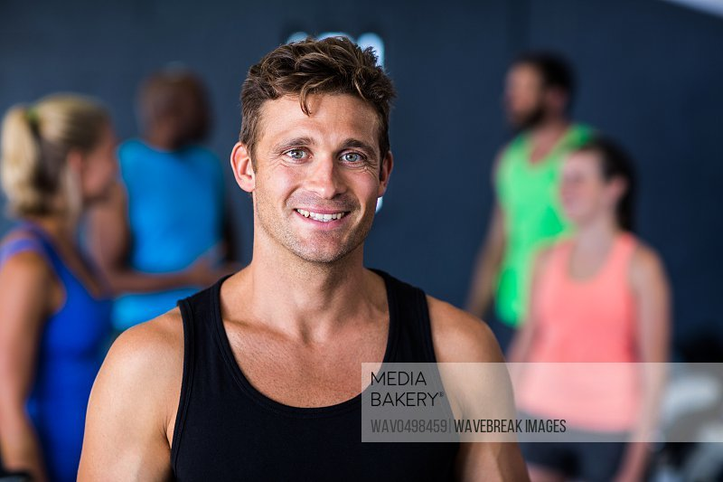 Portrait of happy young man standing in gym