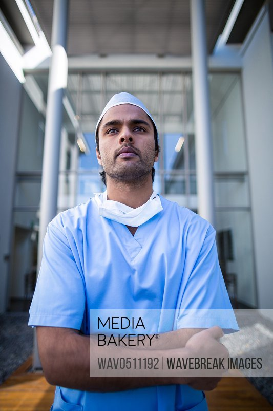 Male surgeon standing with arms crossed in hospital corridor