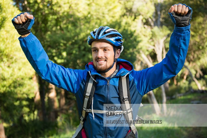 Excited male mountain biker in the forest on a sunny day