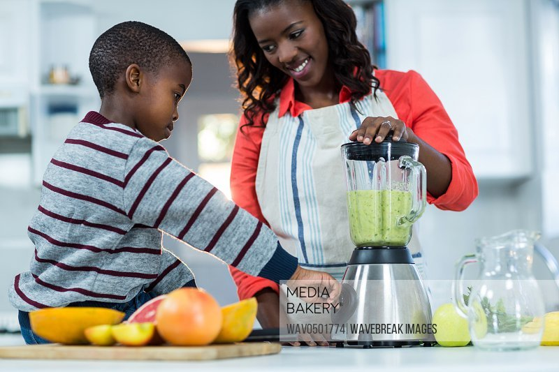 Woman and son using mixer in kitchen